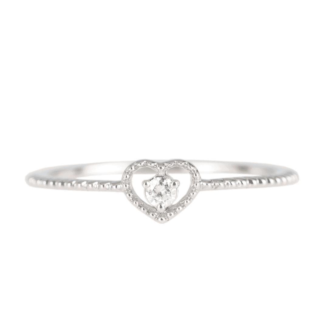 Delikatny pierścionek z białego złota z diamentem na jasnym tle