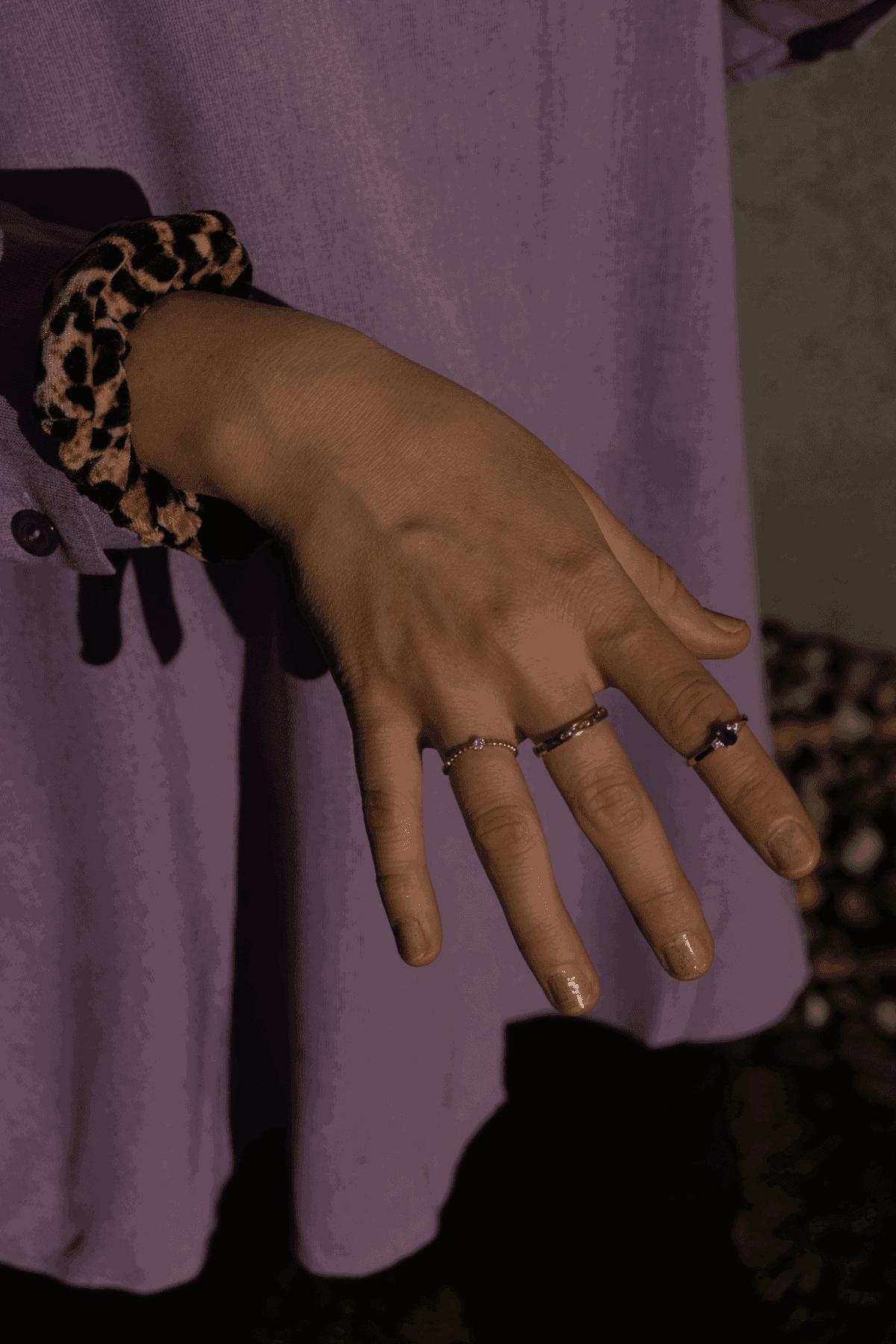 Modelka prezentuje zestaw złotych pierścionków z diamentami i szafirami
