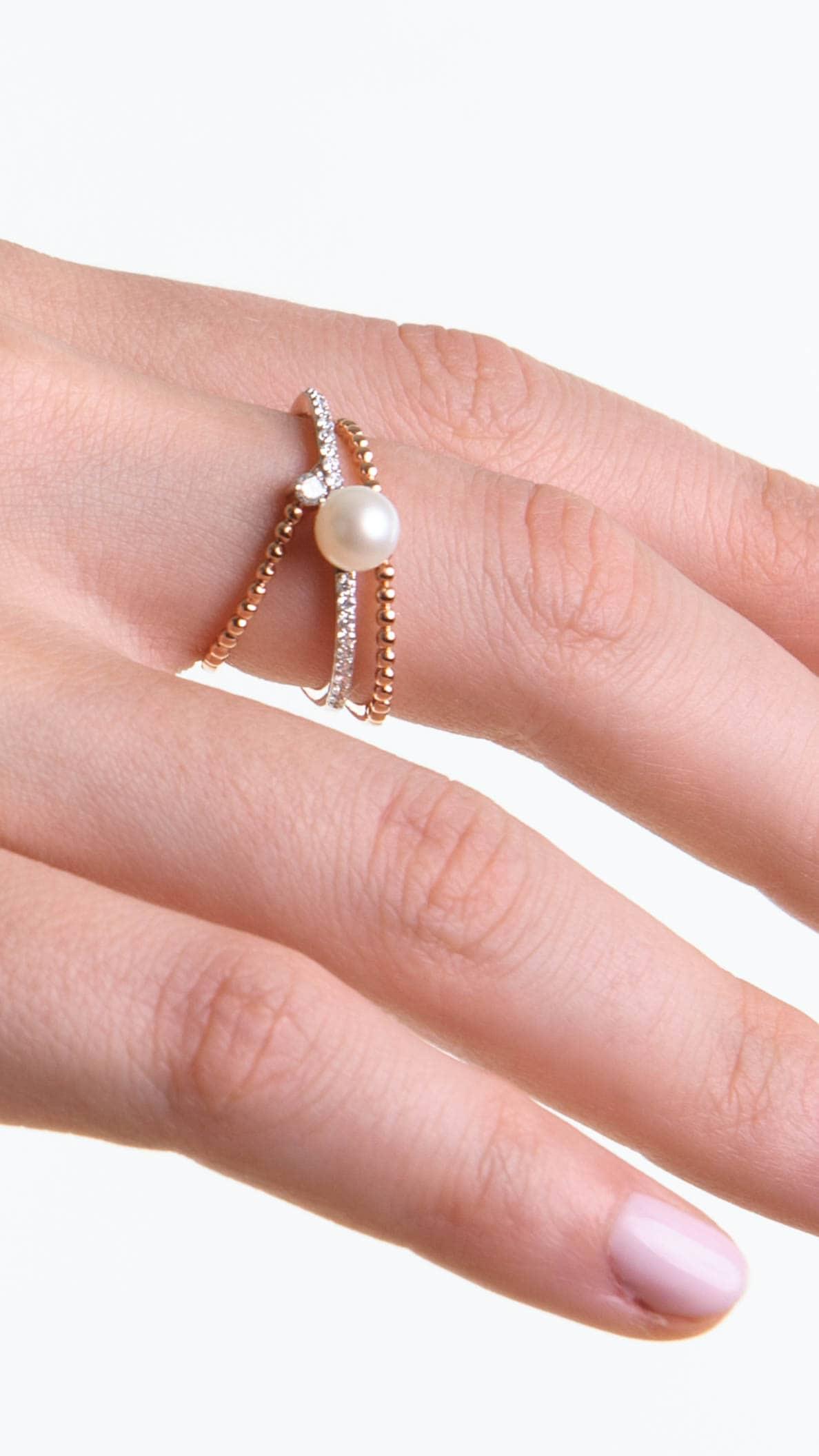 Modelka prezentuje na złoni pierścionek z różowego złota z diamentami i perłą