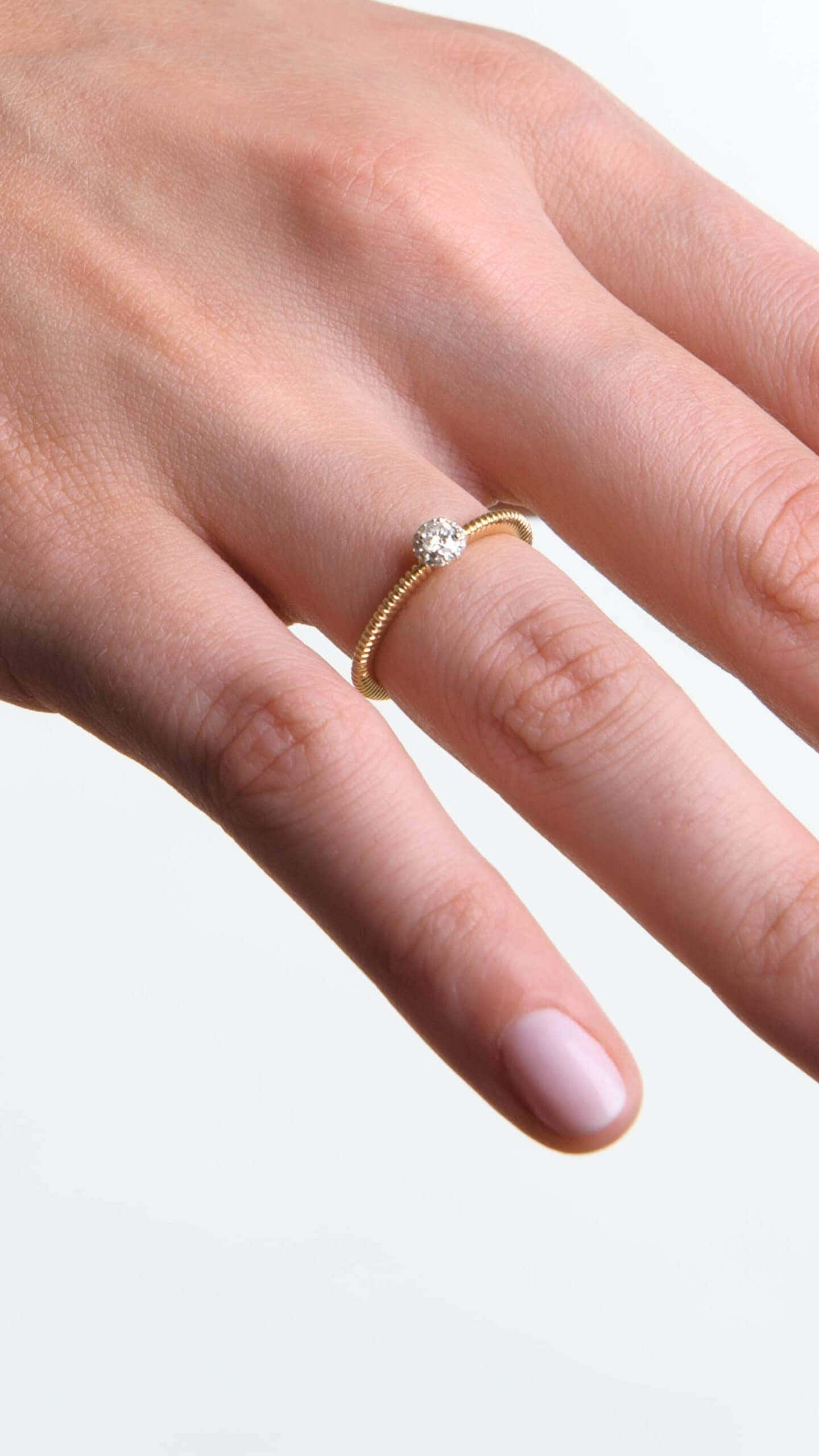 Modelka prezentuje na dłoni złoty pierścionek zaręczynowy z diamentami polskiej marki jubilerskiej.