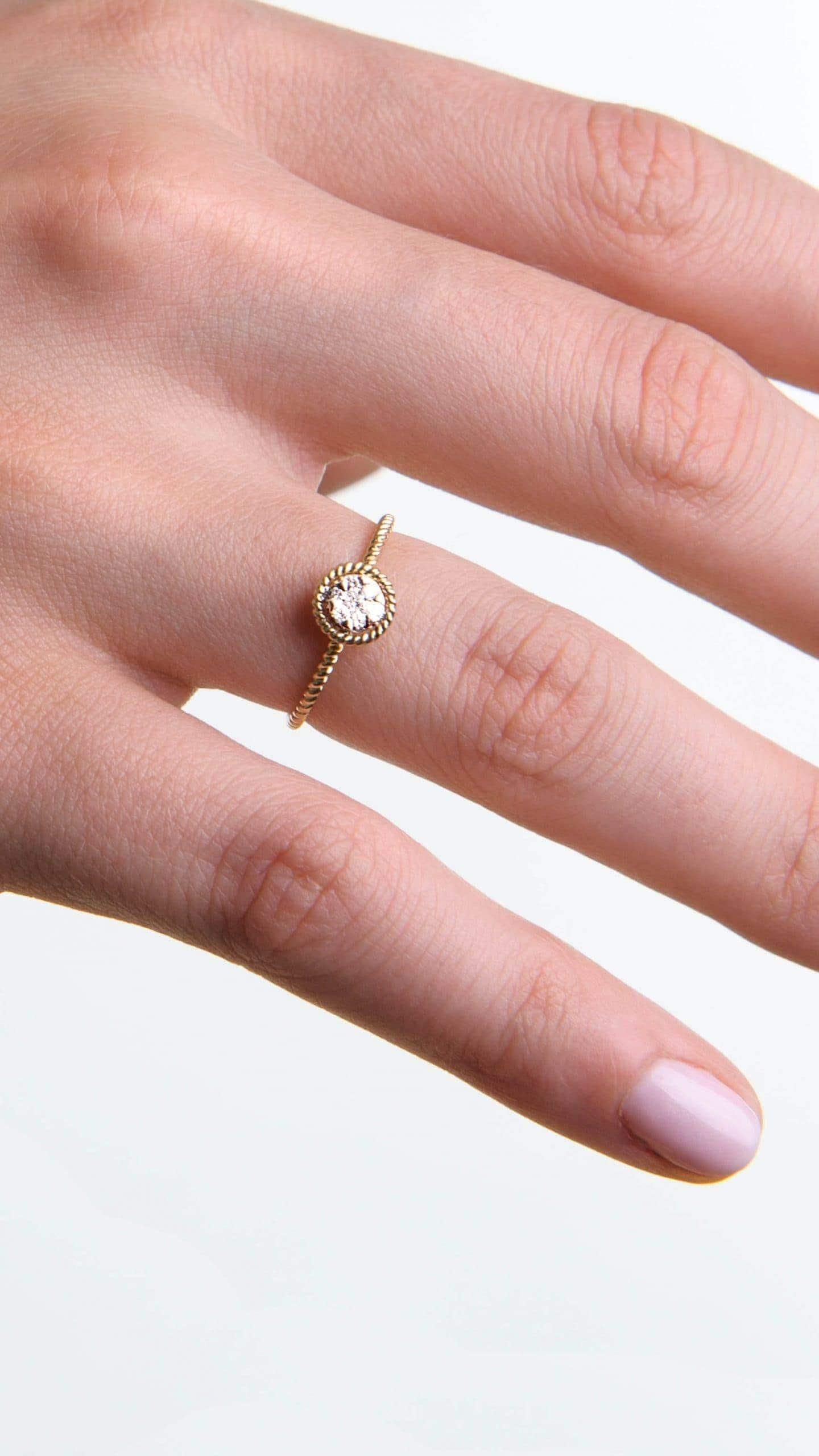 Modelka prezentuje na dłoni złoty pierścionek zaręczynowy z diamentem.