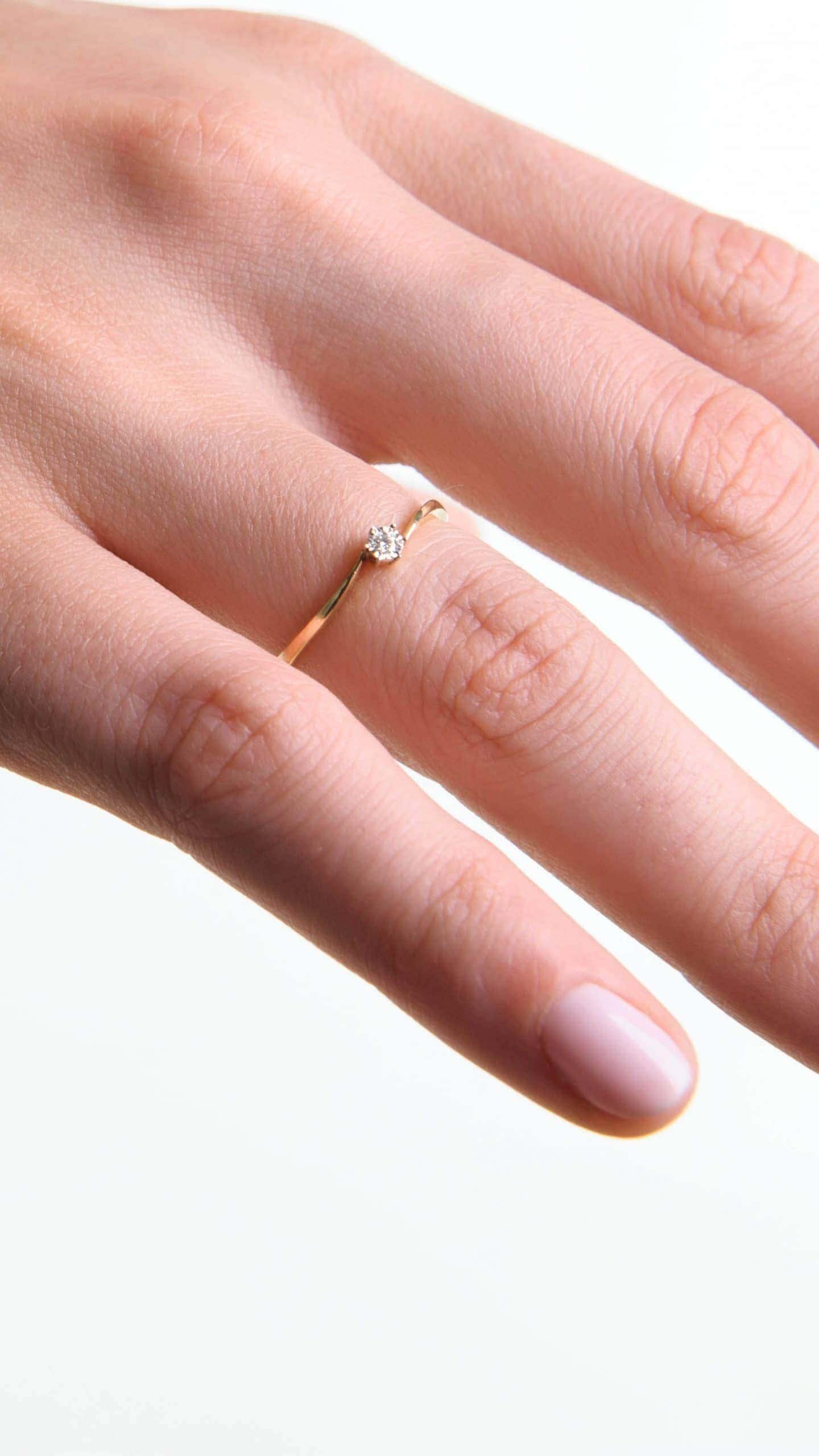 Modelka prezentuje na dłoni złoty pierścionek z diamentem