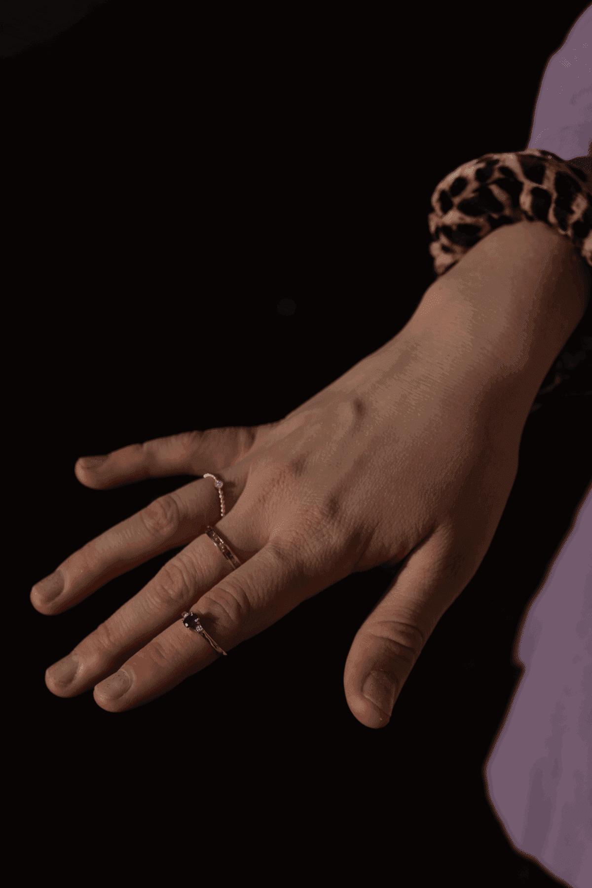 Modelka prezentuje złoty pierścionek z szafirem i diamentami.
