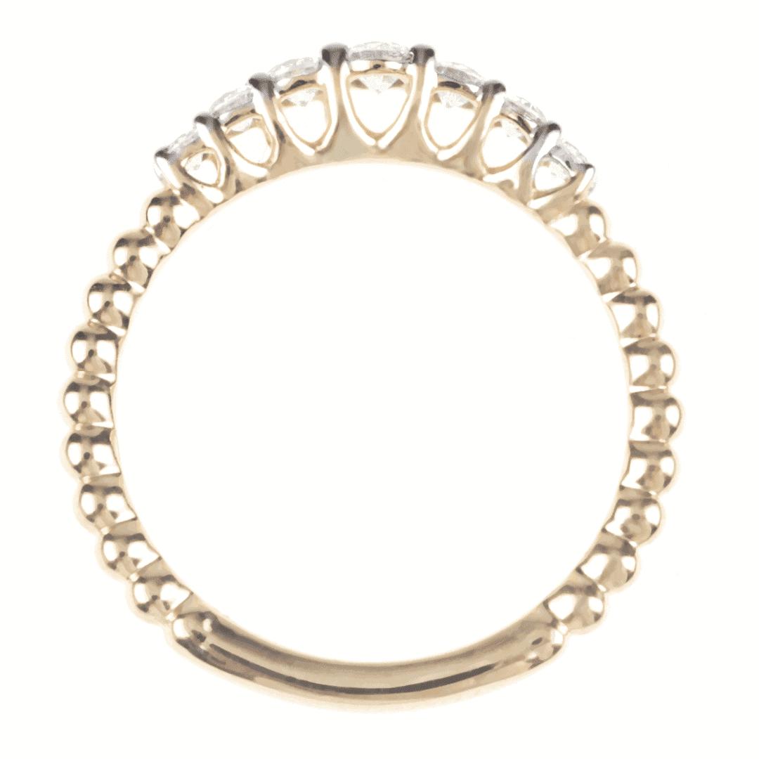 Pierścionek wykonany ze złota z diamentami widok od góry na jasnym tle.