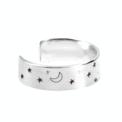 Srebrna nausznica z wygrawerowanymi gwiazdkami i księżycem na jasnym tle.