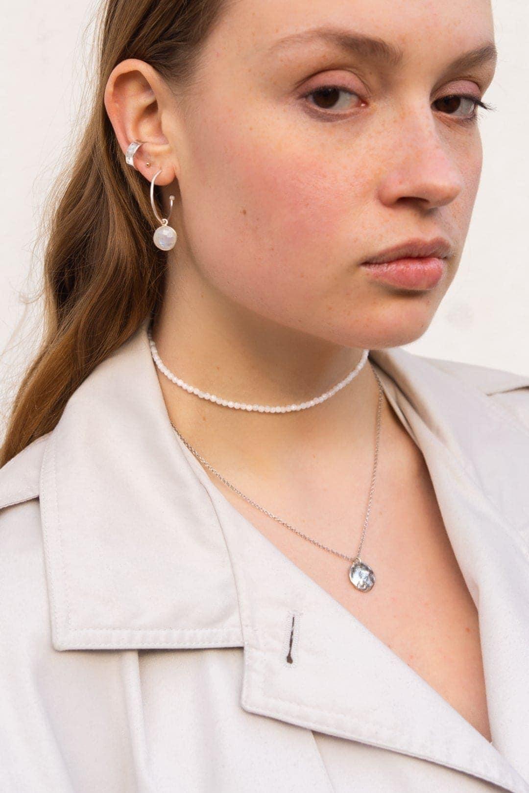 Modelka prezentuje na sobie srebrny naszyjnik księżyc i biały choker z kamieni.