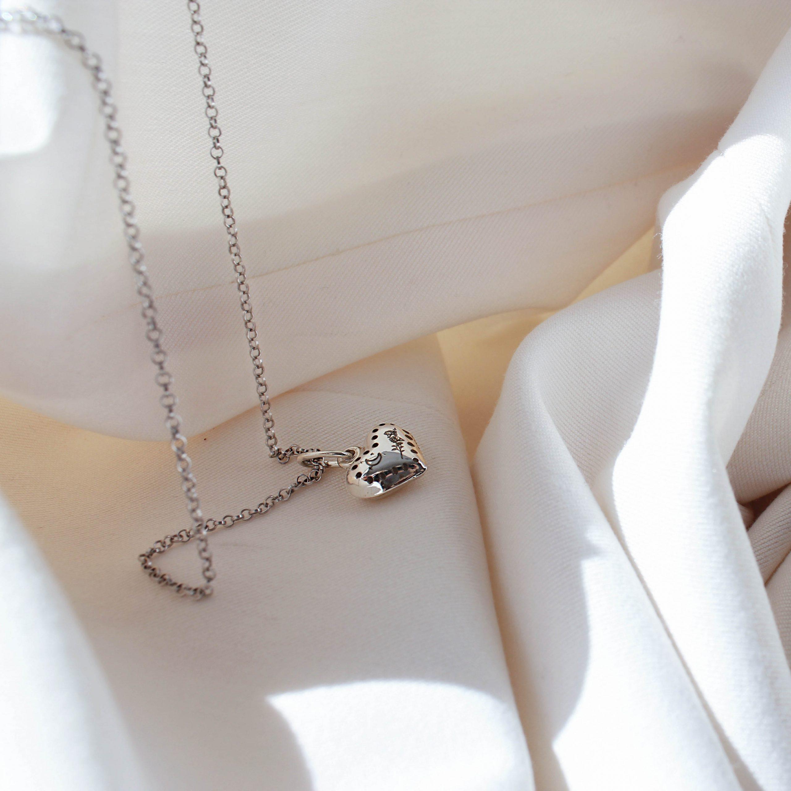 Srebrny naszyjnik z grawerem w kształcie serca z rodowanym łańcuszkiem.