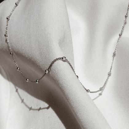 Srebrny łańcuszek kuleczki na jasnym tle