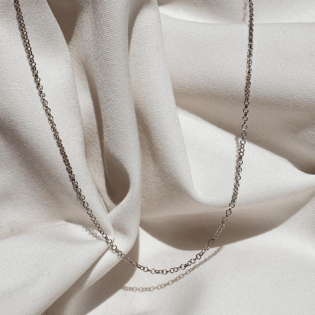 Łańcuszke ze srebra na jasnym materiale.