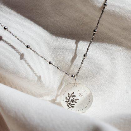 Srebrny naszyjnik z grawerem roślinnym i księżycem.