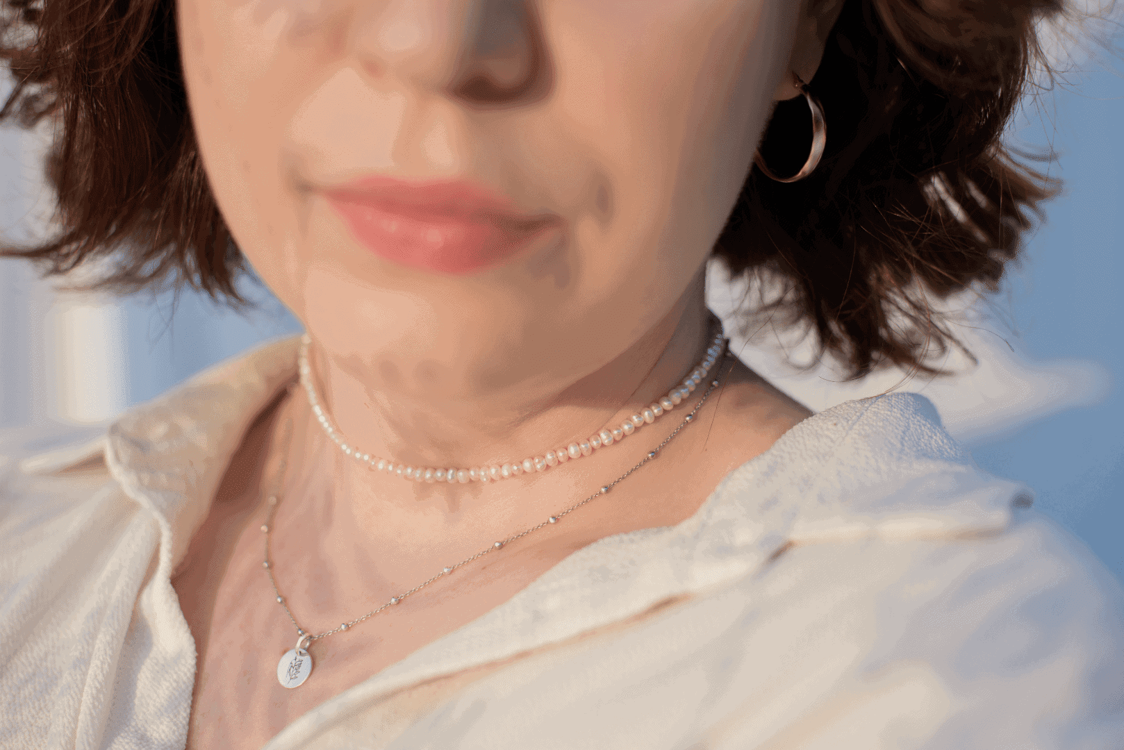 Modelka prezentuje na sobie zestaw biżuterii z pereł, srebra i złota