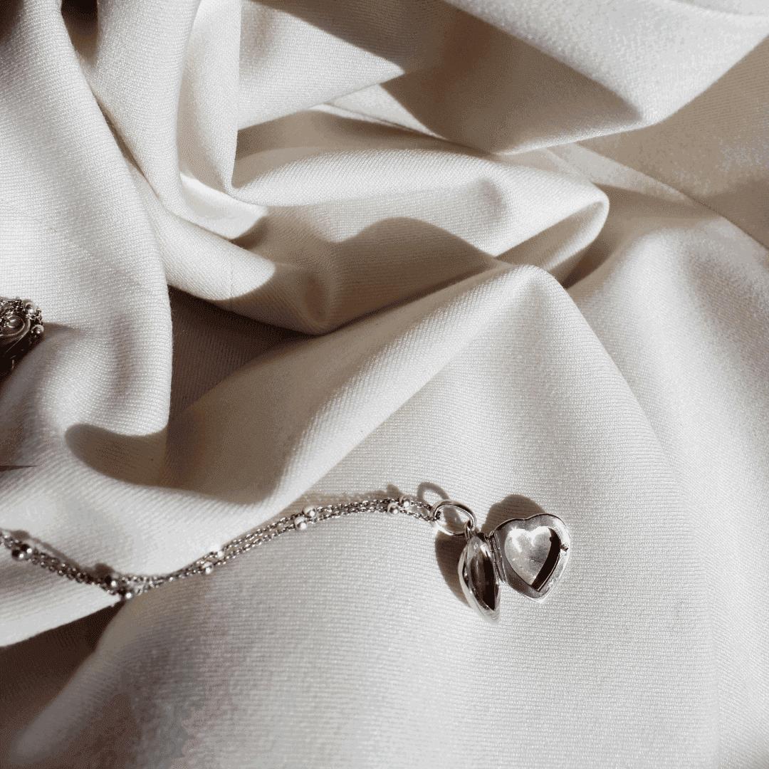 Srebrna zawieszka na fotografie w formie serca na jjasnym materiale