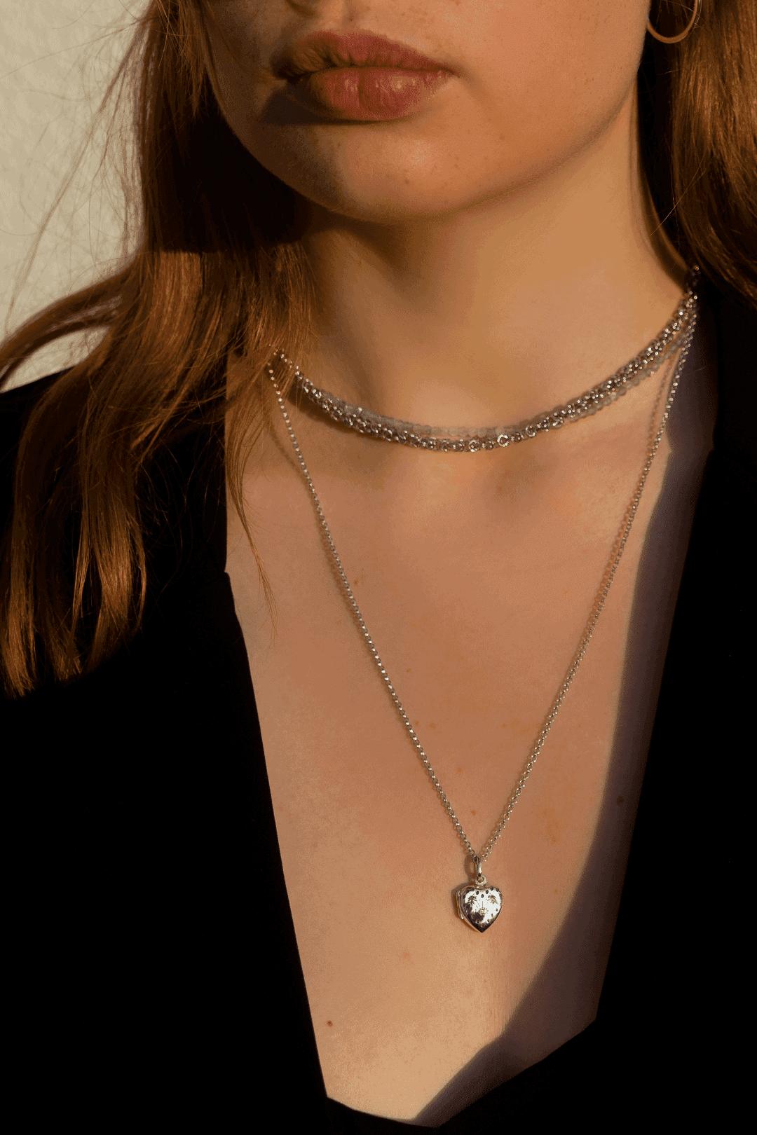 Modelka prezentuje na sobie zestaw srebrnej biżuterii: sekretnik na fotografię, srebrny naszyjnik i naszyjnik z kamieni naturalnych.