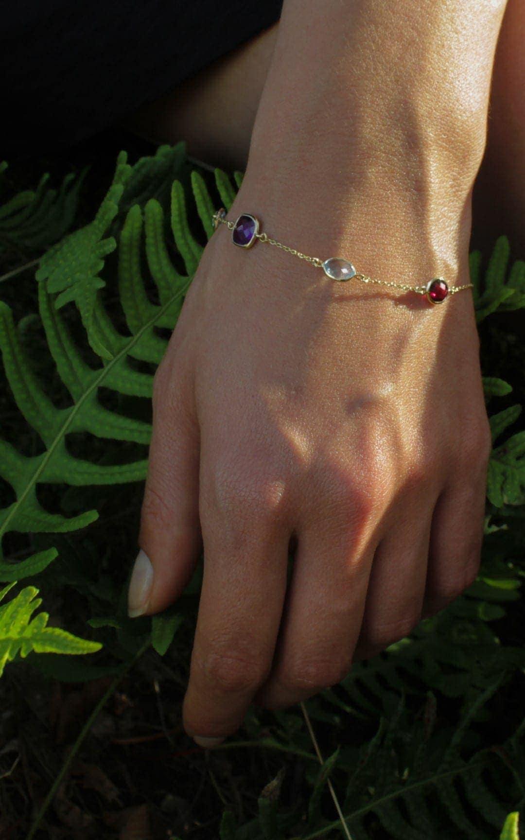 Modelka prezentuje złotą bransoletkę z kolorowymi kamieniami