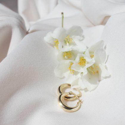 Klasyczne złote kolczyki i białe kwiatki na jasnym materiale