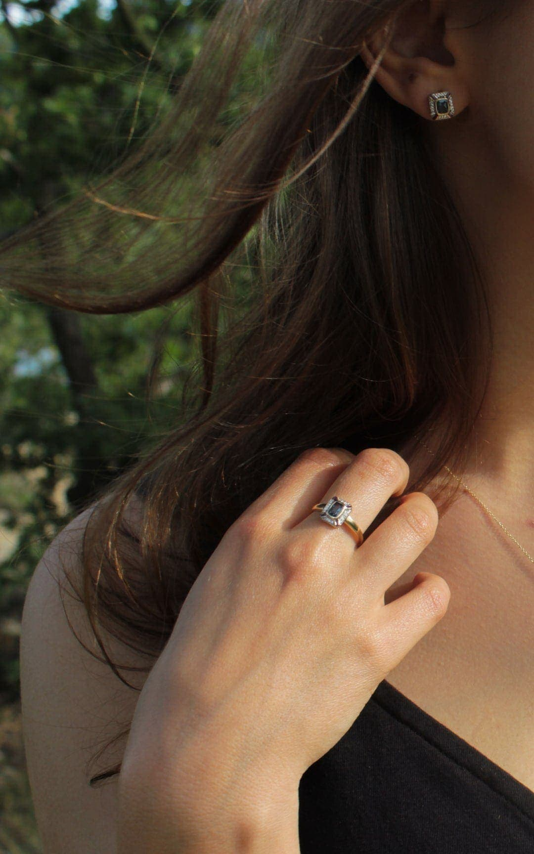 Modelka prezentuje zestaw złotej biżuterii z topazem i diamentami. Ma złoty pierścionek i kolczyki do kompletu.