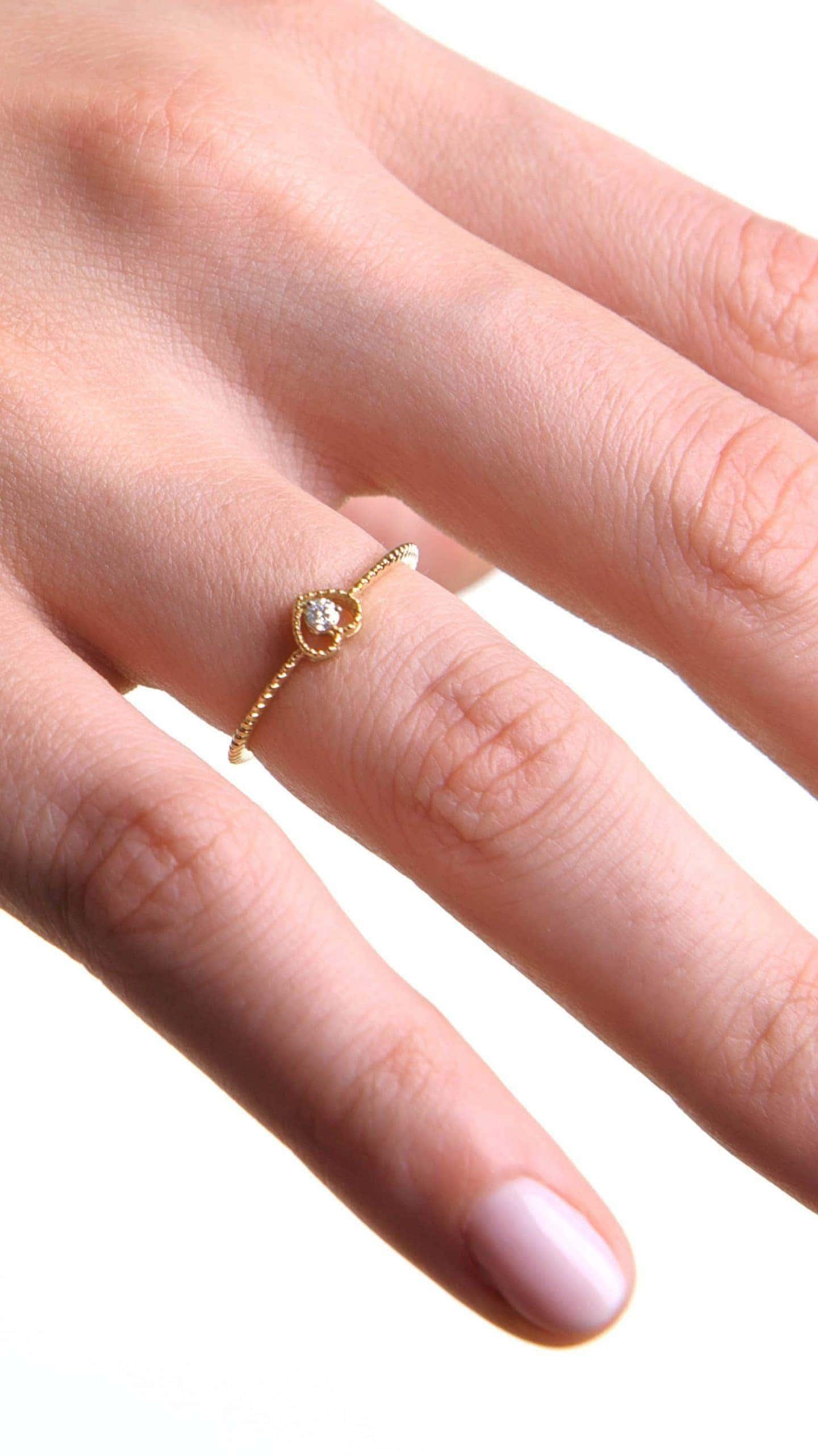 Modelka prezentuje złoty pierścionek z diamentem w formie serca