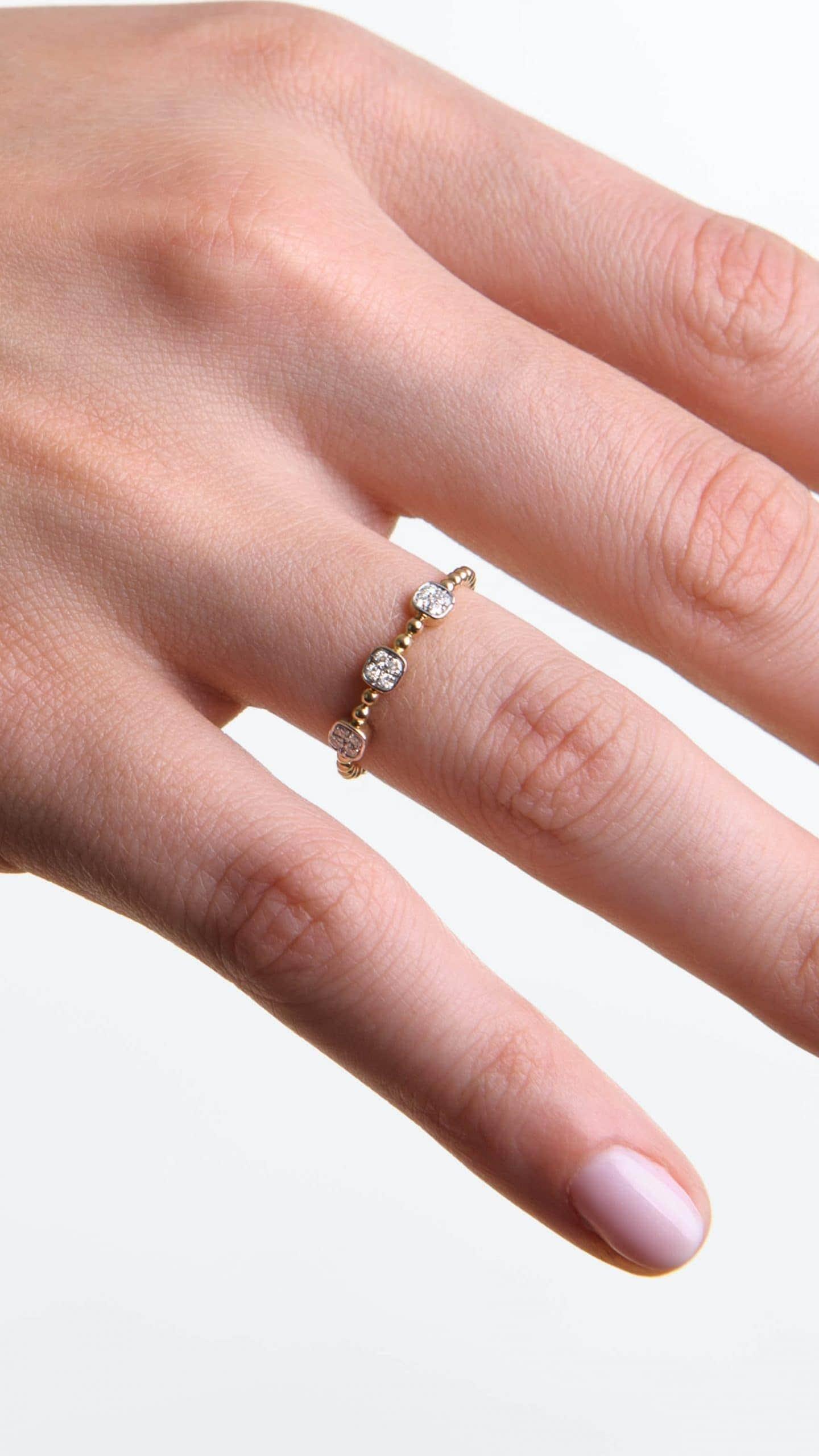Modelka prezentuje na dłoni złoty pierścionek z diamentami