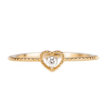 Pierścionek ze złota w kształcie serca z diamentem na jasnym tle.