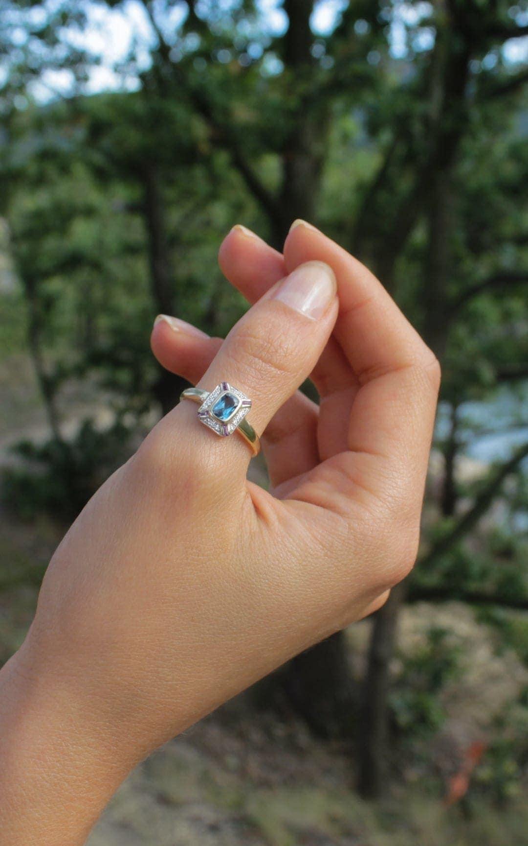 Modelka prezentuje na dłoni złoty pierścionek z topazem i diamentami