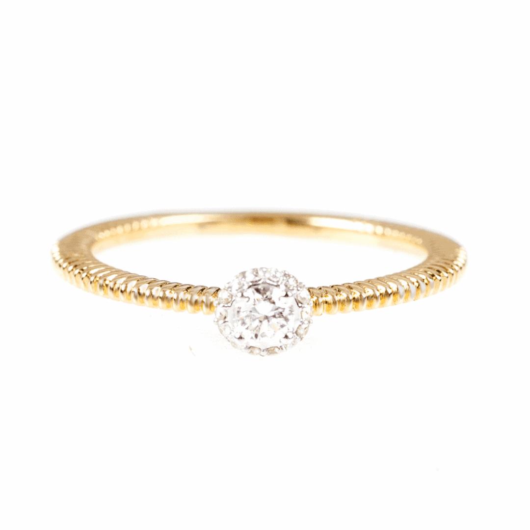 Złoty pierścionek z diamentami na jasnym tle