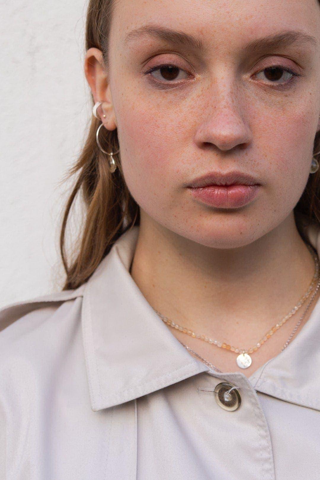 Modelka prezentuje biżuterię autorską z personalizowanym grawerem.
