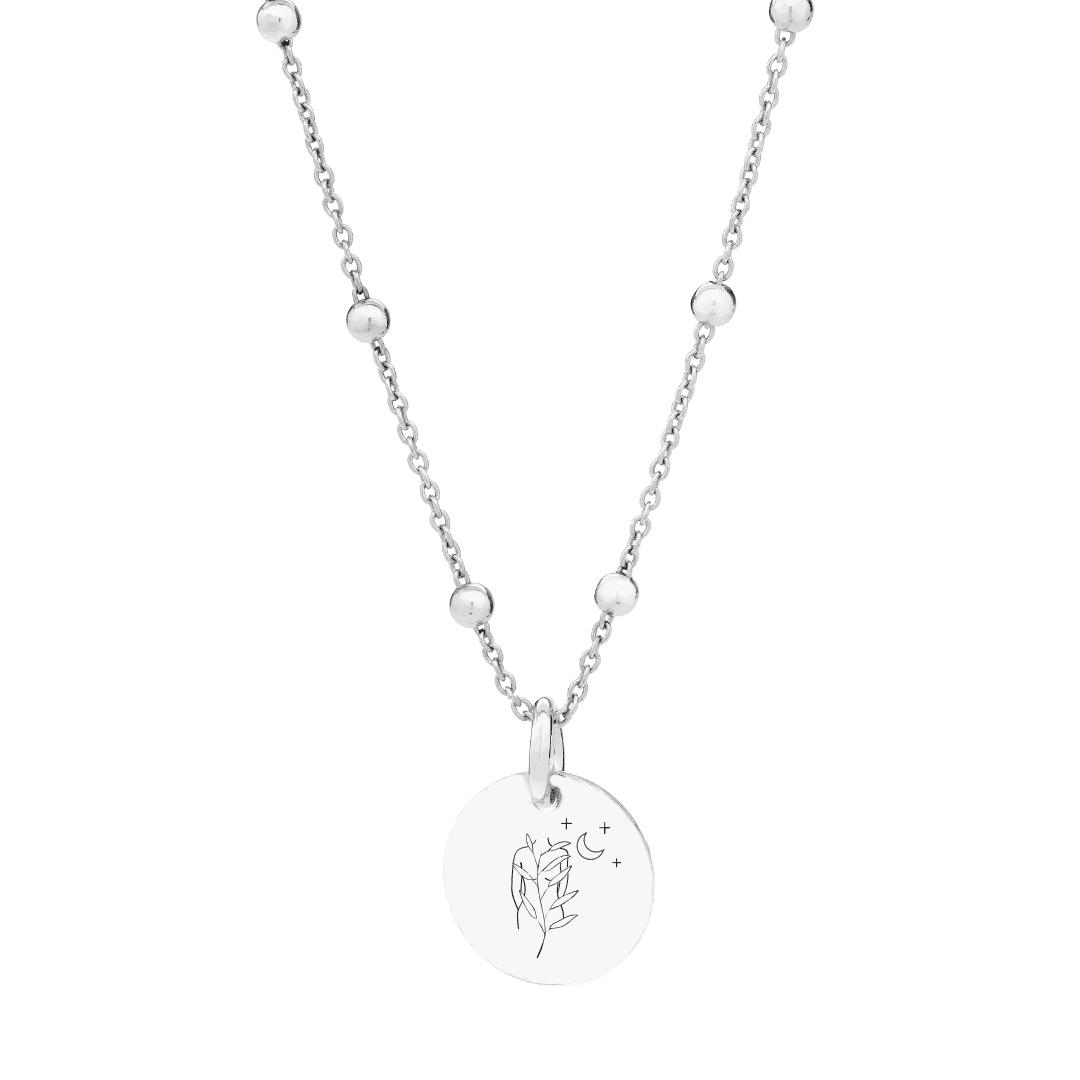 Srebrny naszyjnik z zawieszką i grawerem kobiety z kwiatami, gwiazd i księżyca.