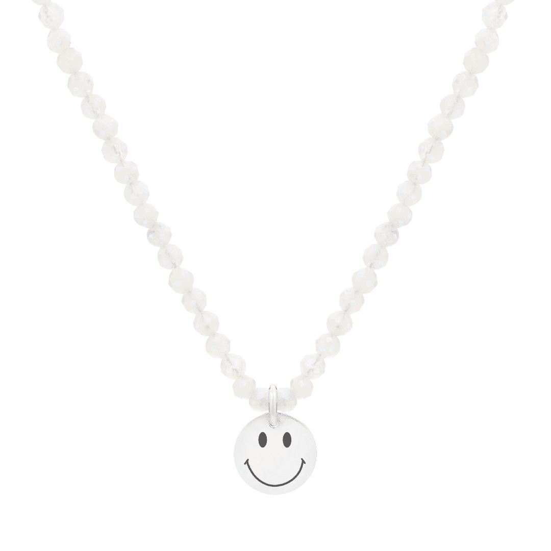 Naszyjnik z białych kamieni z zawieszką z wygrawerowanym uśmiechem.