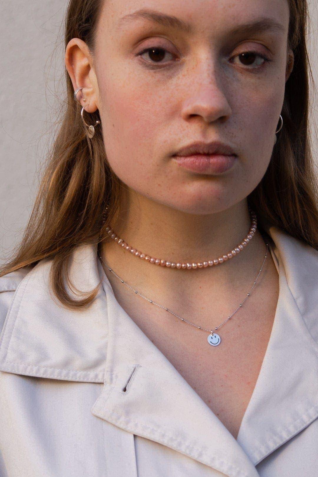 Modelka prezentuje zestaw naszyjników: choker z pereł, naszyjnik z grawerem i srebrne kolczyki koła z zawieszką.