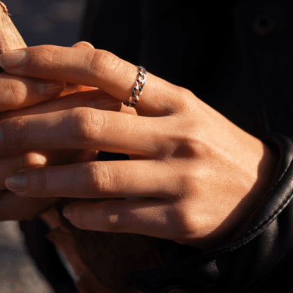 Modelka prezentuje na dłoni srebrny pierścionek łańcuch trzymając suchy liść.