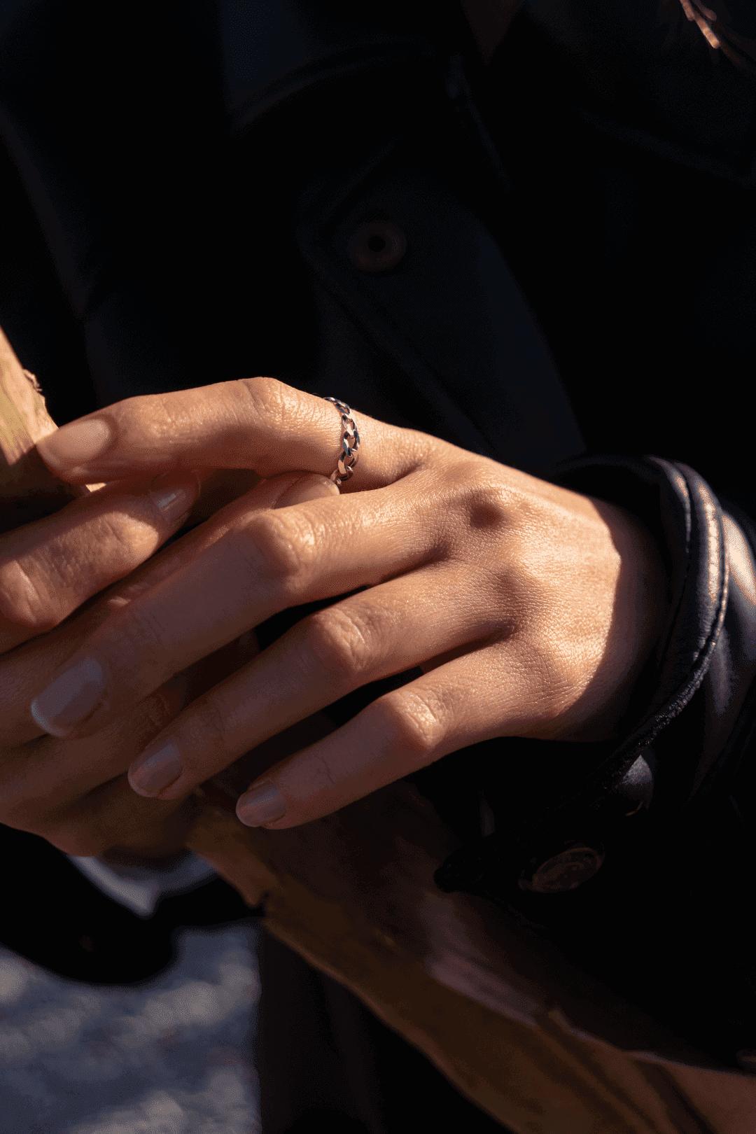 Modelka w czarnej kurtce prezentuje srebrny pierścionek łańcuch polskiej marki jubilerskiej.