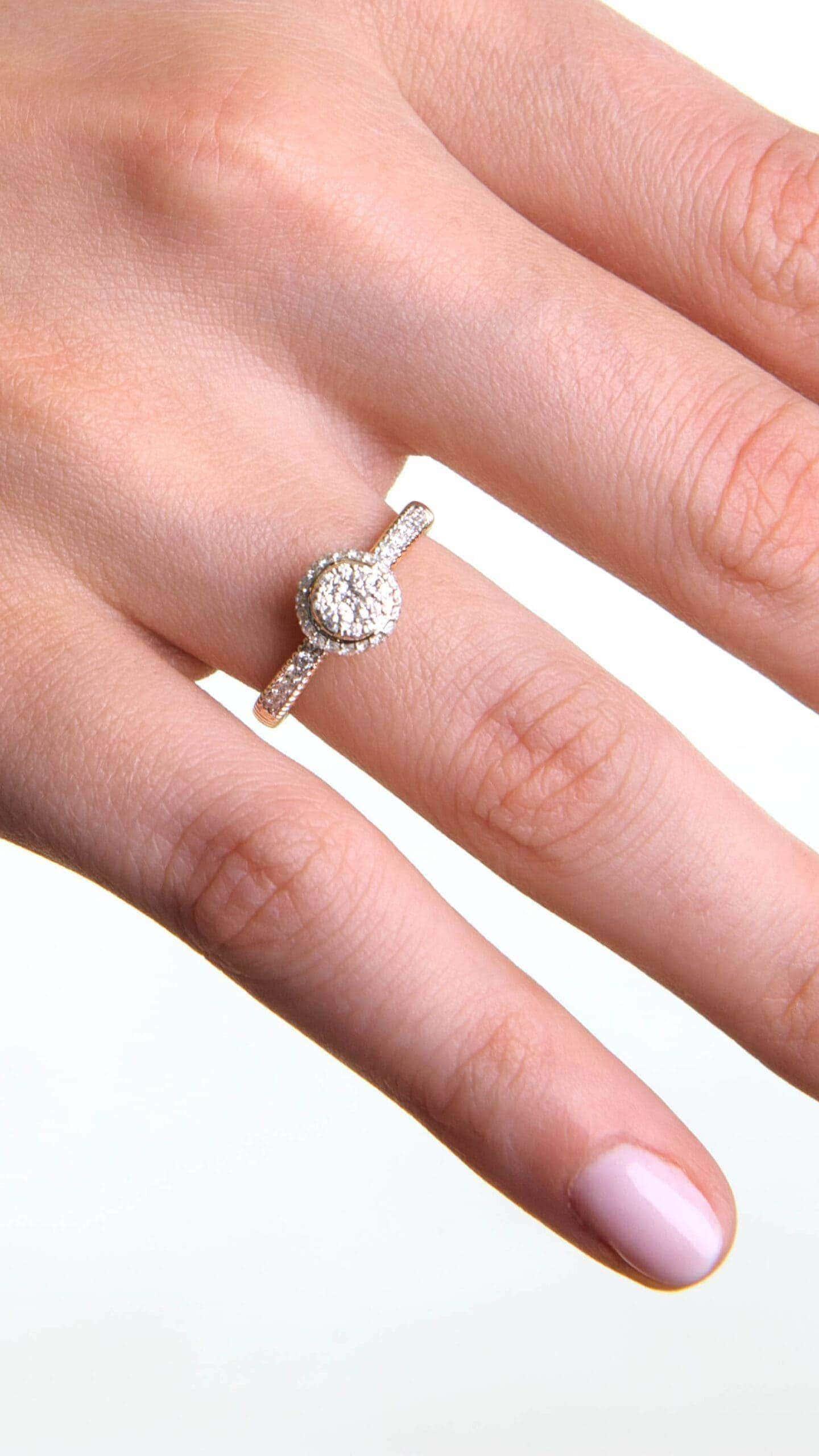 Modelka prezentuje na dłoni złoty pierścionek zaręczynowy z diamentami.