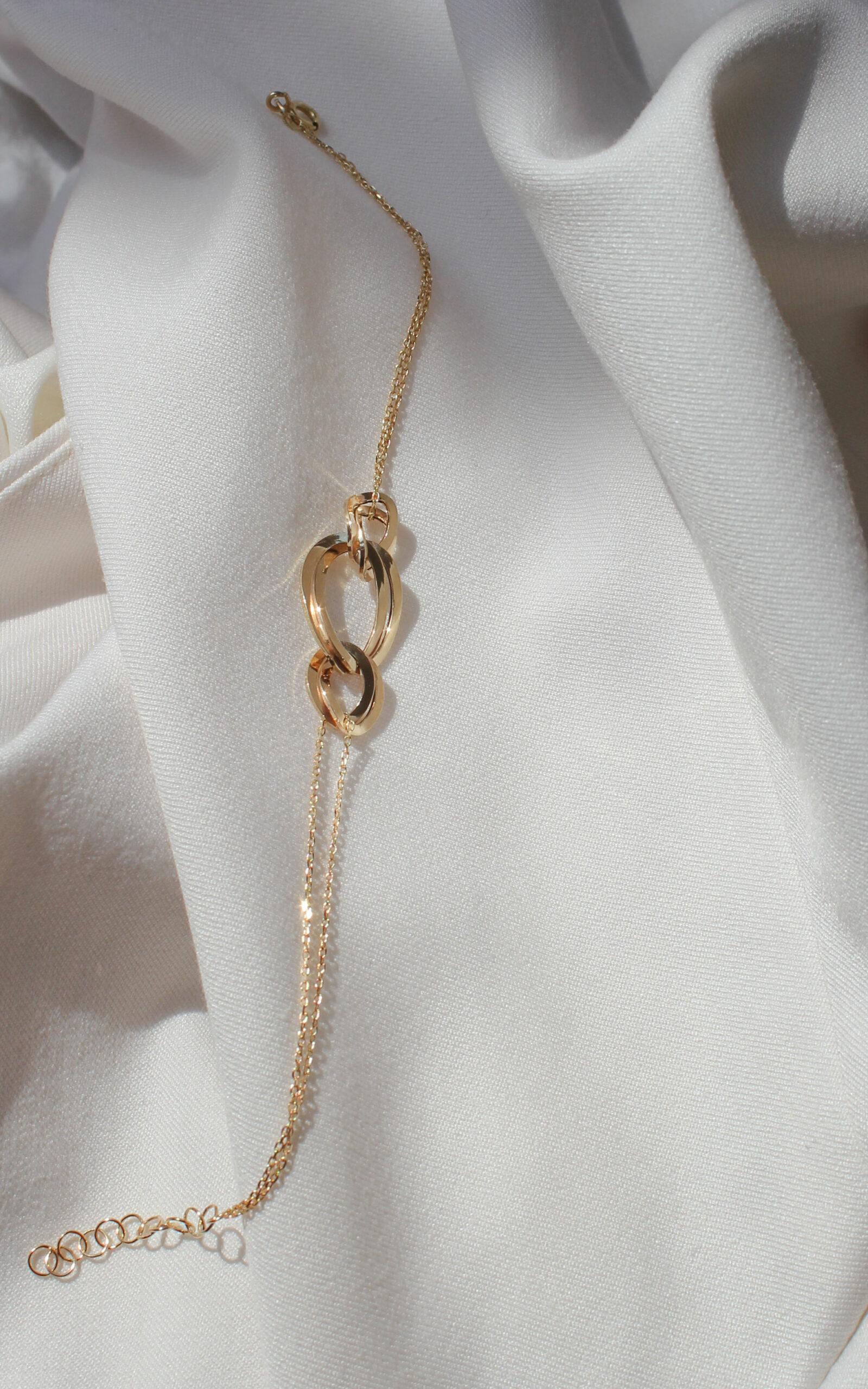 Złota bransoletka łańcuch na jasnym materiale.