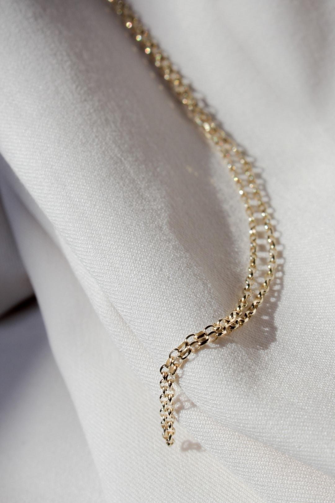 Złoty łańcuszek na janym tle.