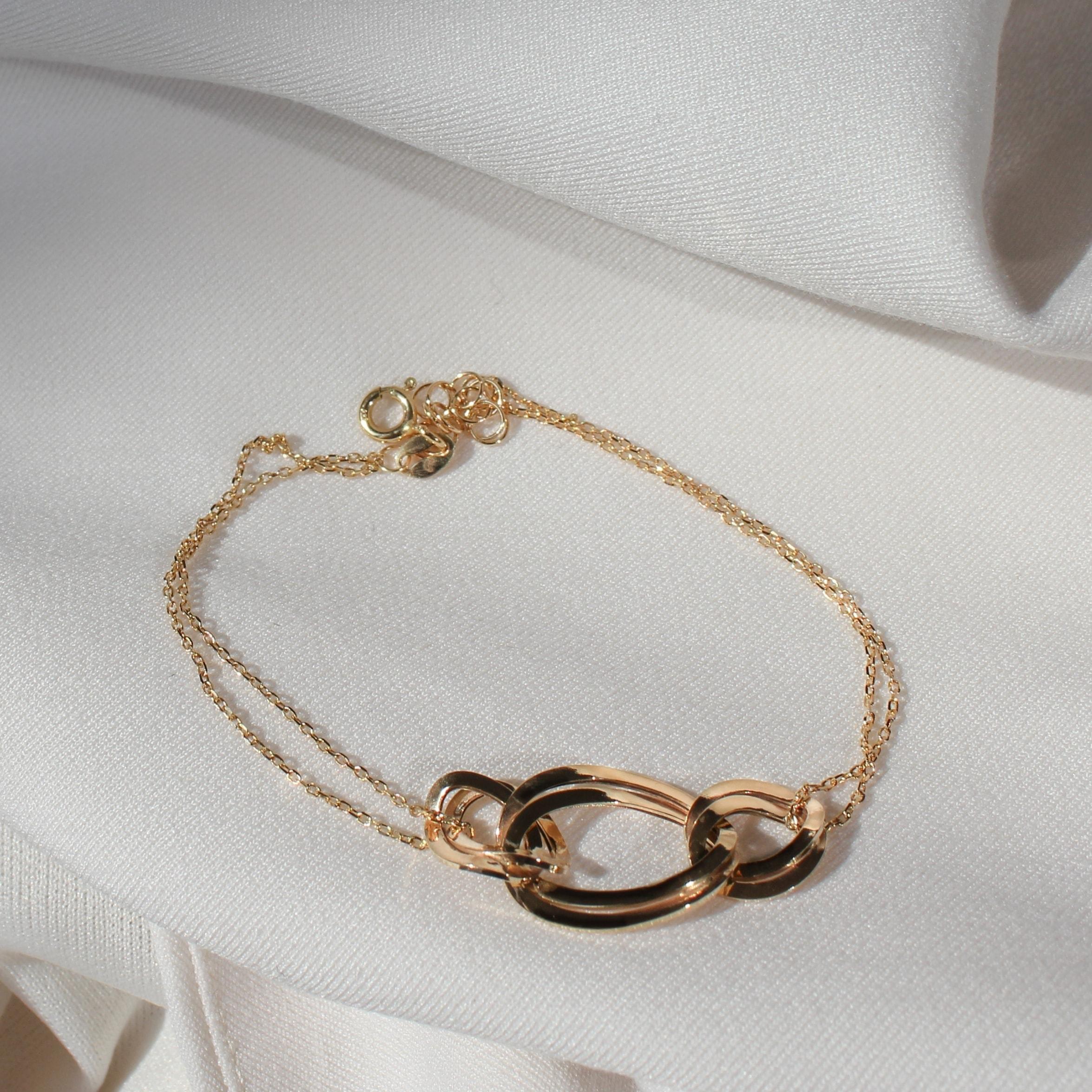Złota bransoletka z łańcuszków na jasnym materiale