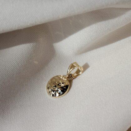 Złota zawieszka na jasnym materiale polskiej marki jubilerskiej.