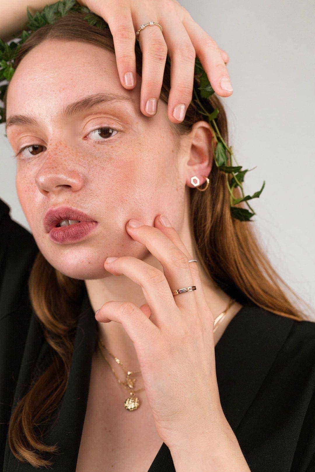 Modelka prezentuje zestaw złotej biżuterii autorskiej.