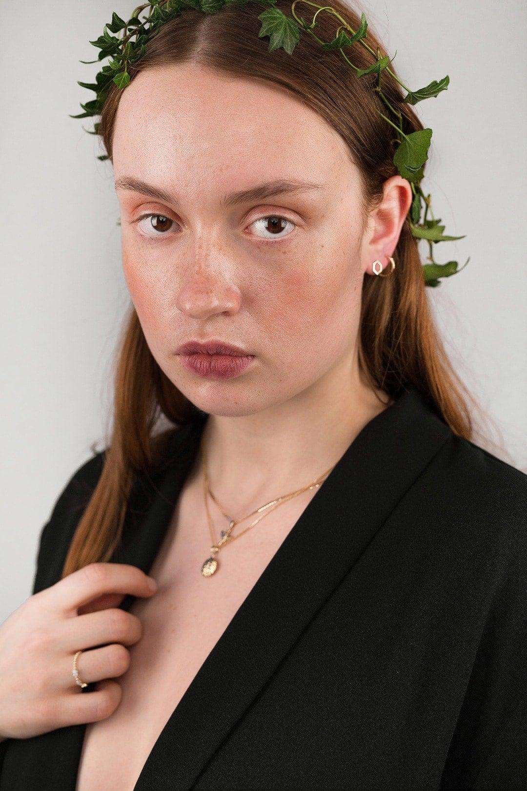 Modelka prezentuje na sobie zestaw złotej biżuterii