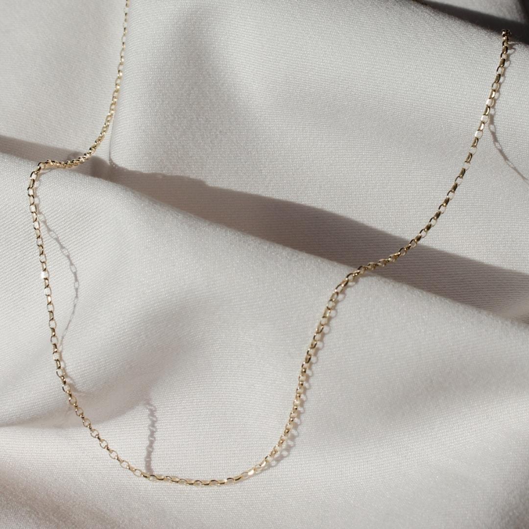 Złoty łańcuszek o klasycznym splocie na jasnym materiale