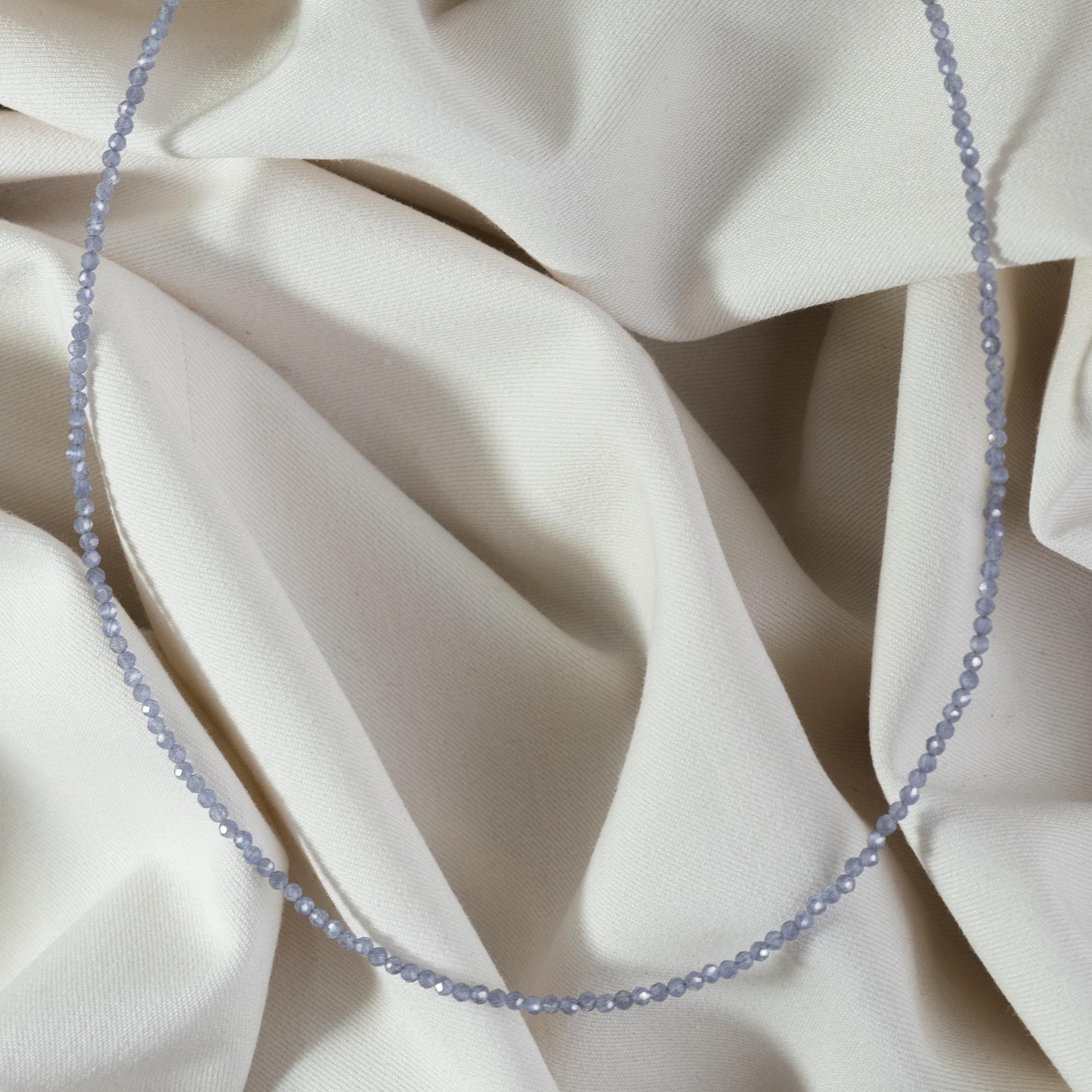 Fioletowy naszyjnik z tanzanitem na jasnym materiale