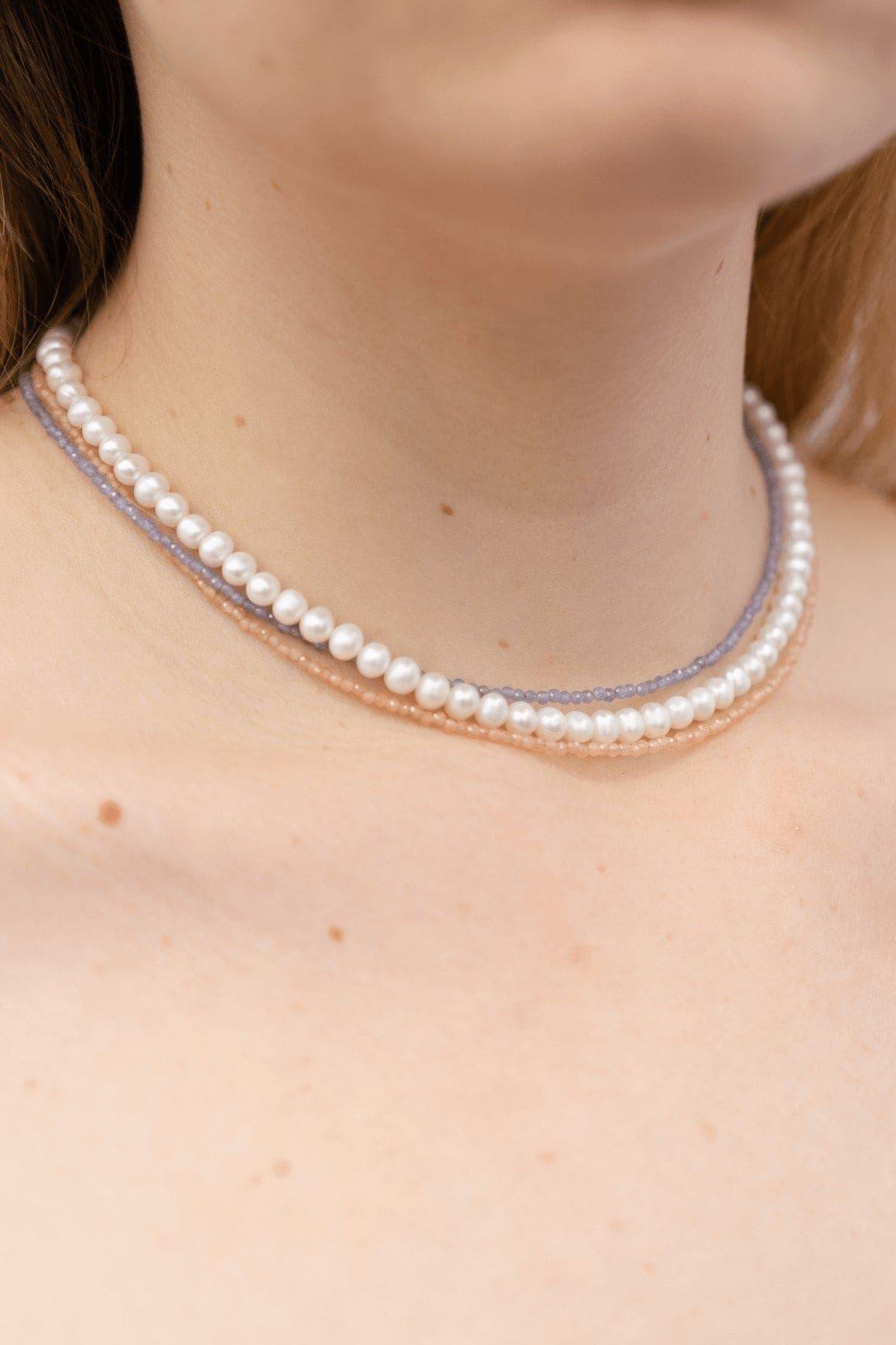 Monika ma na sobie naszyjniki z kolorowych kamieni naturalnych oraz naszyjnik z pereł
