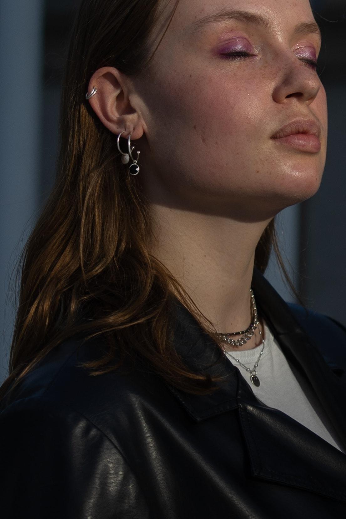 Modelka prezentuje srebrne kolczyki koła z zawieszką oraz nausznice.