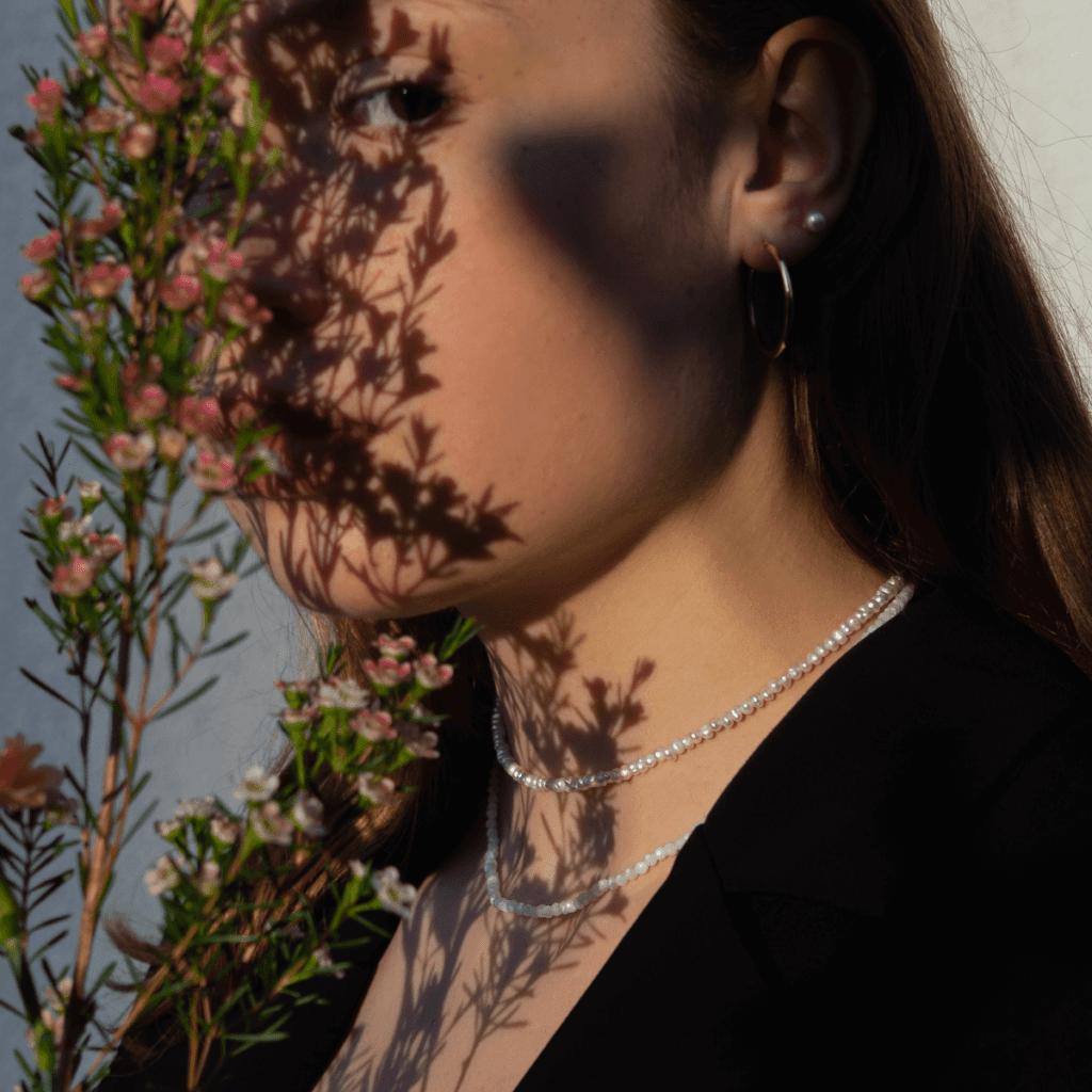 Modelka prezentuje naszyjnik z kamieniem księżycowym oraz choker z pereł