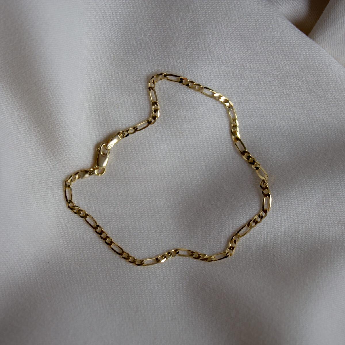 Złota bransoletka o splocie figaro na jasnym materiale.