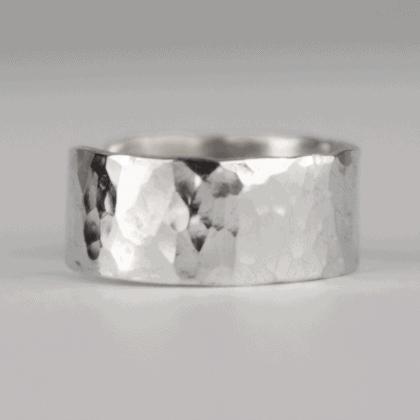 Srebrna nausznica ręcznie robiona biżuteria na szarym tle.
