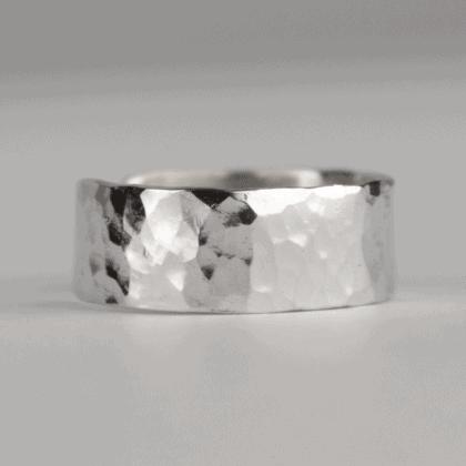 Srebrna nausznica ręcznie robiona biżuteria autorska na szarym tle